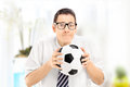 Anxious young sports fan watching football match and holding bal Stock Image