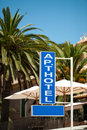 Apart hotel sign on a pillar with umbrellas palm trees behind Royalty Free Stock Photos