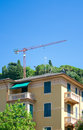Apartment house, heron on the roof and crane, Rapallo, Italy Royalty Free Stock Photo