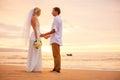 Apenas pareja casada que lleva a cabo las manos en la playa en la puesta del sol Fotos de archivo libres de regalías