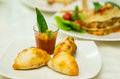 Apetizer of small tomato soup in shotglass and delicious mini empanadas spread around on white plate Royalty Free Stock Photo