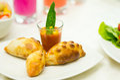Apetizer of small tomato soup in shotglass and delicious mini empanadas spread around on white plate Royalty Free Stock Photo