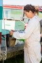 Apiculteur fueling smoker for enlevant le miel Photographie stock