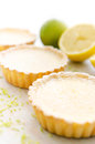 Appetising lemon tarts delicious looking with lime zest and a cut Stock Photos