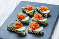 Appetizer canape with chopped vegetables and sesame on stone slate background close up Royalty Free Stock Photo