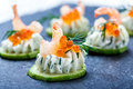 Appetizer canape with red caviar, shrimp and cream cheese on stone slate background close up.
