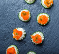 Appetizer canape with salmon, cucumber and cream cheese on stone slate background close up.
