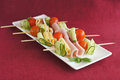 Appetizer with ham cucumber cheese and tomatoes cherry on sticks on white plate on red background Stock Images