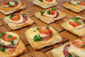 Appetizer of puff pastry with salami cheese and cherry tomatoes Royalty Free Stock Photography