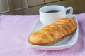 Appetizing bread and cup of coffee on table Royalty Free Stock Images