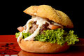 Appetizing burger beef with onions lettuce and tomato served on red plate Stock Images