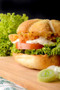 Appetizing burger fish with leek lettuce and tomato served on wooden board Stock Photos