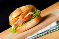 Appetizing burger fish with lettuce and tomato served on wooden board Stock Photography
