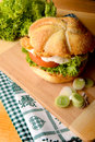 Appetizing burger with leek fish lettuce tomato and cream sauce served on wooden board Stock Photos