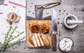 Appetizing chicken cooked in mustard sauce and cut into slices on a cutting board a knife, herbs, salt and pepper unmilled on Royalty Free Stock Photo