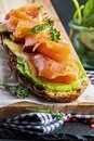 Appetizing and healthy smoked salmon with avocado and vegetables spinach sprouts, tomatoes, thyme on toast. Homemade look Royalty Free Stock Photo