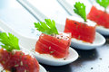 Appetizing tuna morsel on ceramic spoons macro close up of row of multiple starters Stock Image