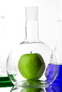 Apple in beaker chemistry laboratory gmo concept Stock Photos