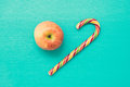 Apple and candy cane on turquoise wooden background top view filter effect Stock Image