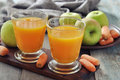 Apple and carrot juice in glass with fresh vegetables fruits on wooden background Stock Images