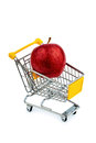 Apple in cart an is a shopping photo icon for the purchase of healthy vitamin rich foods Royalty Free Stock Photos