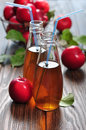 Apple cider in glass bottle and basket with fresh apples Stock Image