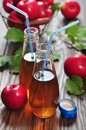 Apple cider in glass bottle and basket with fresh apples Royalty Free Stock Photos
