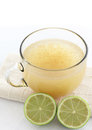 Apple cider next to green lemons Royalty Free Stock Images