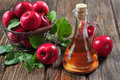 Apple cider vinegar in glass bottle and basket with fresh apples Royalty Free Stock Photos