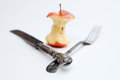 Apple core and cutlery an antique fork knife on white background Royalty Free Stock Photo