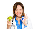 An apple a day keeps the doctor away closeup portrait of beautiful smiling female health care professional holding isolated on Stock Images