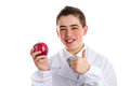 Apple a day keeps the doctor away old saying an acne skin child with medical white coat is showing juicy red making success sign Royalty Free Stock Photo