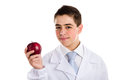 Apple a day keeps the doctor away old saying an acne skin child with medical white coat is showing juicy and tasty red reminding Royalty Free Stock Images