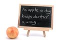 An apple a day keeps doctor away sayings written on blackboard Stock Image