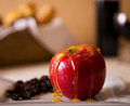 An apple drizzled with honey Royalty Free Stock Photo