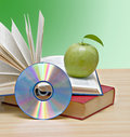 Apple, dvd, and books Royalty Free Stock Photo
