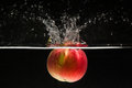 Apple falling in water Royalty Free Stock Photo