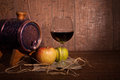 Apple , glass of red wine and barrel on rustic Royalty Free Stock Photo
