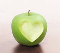 Apple with heart shape isolated on wood background Royalty Free Stock Photography