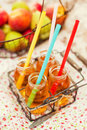 Apple juice with colorful straws Stock Images