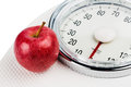 Apple lies on a balance personal scale is an symbolic photo for weight loss and healthy vitamin rich diet Stock Images