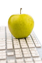 Apple lies on a keyboard an is computer symbolic photo for healthy and vitamin rich snack Royalty Free Stock Images