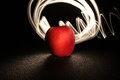 Apple and light on black with long exposure effects Stock Photography