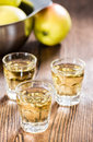 Apple liqueur shot close up on dark wooden background Stock Photos