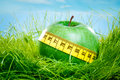 Apple and measuring tape green on the green grass Stock Images