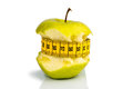 Apple with measuring tape on a symbolic photo for diet and healthy vitamin rich diet Royalty Free Stock Images