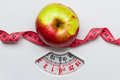 Apple with measuring tape on weight scale. Dieting Royalty Free Stock Photo