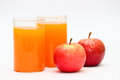 Apple and orange fruit juice two glasses full of fresh citrous a pair of red healthy apples as diet food Stock Image