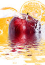 Apple and orange splash Stock Photography
