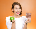 Apple over chocolate closeup portrait beautiful smiling young woman offering nutritious lime as an alternative to unhealthy square Stock Images